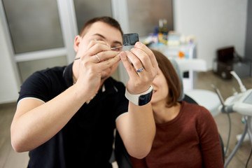 Dentist shows the patient the features of the x-ray of the teeth shot in a modern dental office. Focus on x-ray picture
