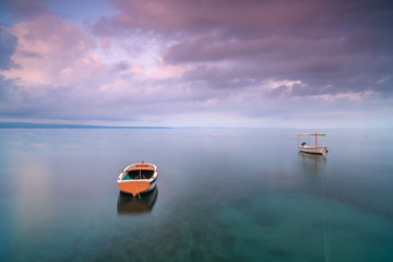 Two boats in adriatic sea at sunrise,long exposure
