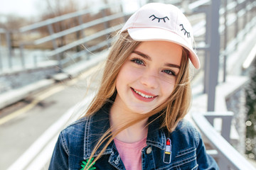 Portrait closeup beautiful young girl in city. Smiling girl in hat