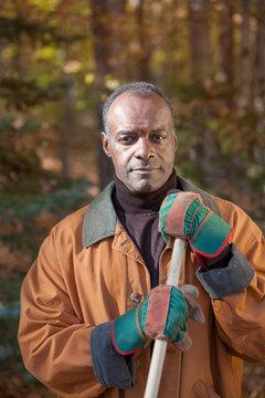 Serious Senior African American Black Man Raking Leaves