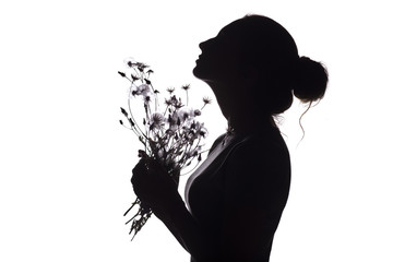 silhouette of a girl with a bouquet of dried flowers, face profile of a dreamy woman looking upwards on a white isolated background
