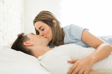 Female Kissing Man On Mouth While Reclining In Bed