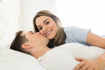 Attractive Woman Being Kissed By Man On Cheek In Bed