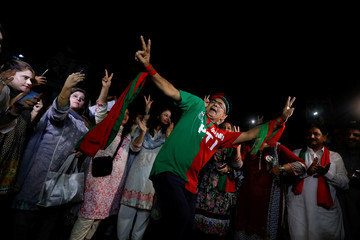 A supporter of cricket star-turned-politician Imran Khan, chairman of Pakistan Tehreek-e-Insaf, reacts to party songs with others, as they celebrate a day after the general election in Karachi,