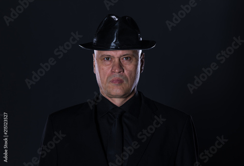 Studio Portrait Of A 50 Year Old Man In Black Clothes On A Black