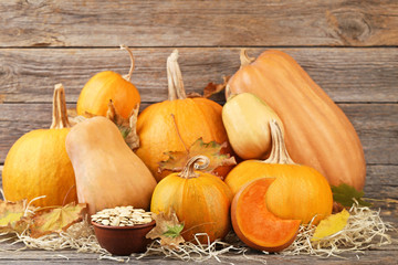 Orange pumpkins with dry leafs and seeds on grey wooden table
