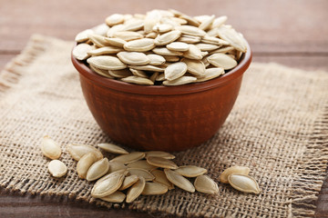 Pumpkin seeds in bowl on wooden table