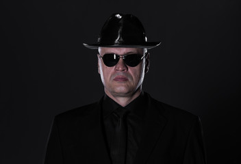 studio portrait of a 50 year old man in black clothes on a black background