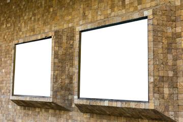 Dos vallas publicitarias en blanco unidas a una pared de ladrillo al exterior de edificio.