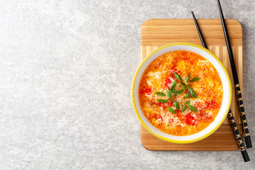 Traditional chinese egg drop soup with tomato and green onion in bowl on gray stone background