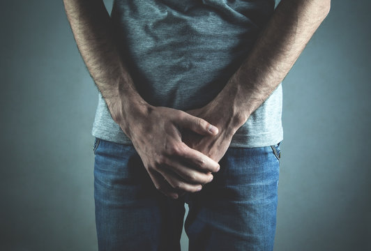 Caucasian man with hands holding his crotch. Inflammation of the prostate, erection problems