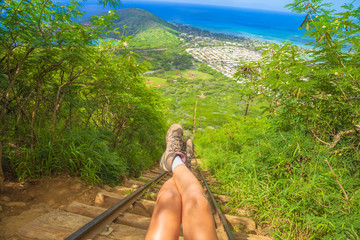 Legs of traveler sitting at the beginning of 1048 steps of popular Hawaiian hiking, koko head stairs hike. Hiking boots on stairway of scenic trekking in Oahu, Hawaii, United States. Freedom concept.