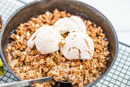 Homemade cooked rhubarb and apple crumble with oatmeal and vanilla ice cream