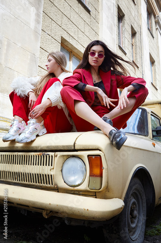 Two fashion young girl siting on the old car   Stylish woman