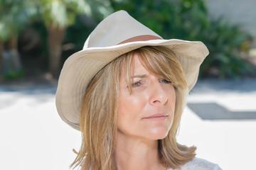 Beautiful woman looks away wearing cowboy hat on patio in bright sunshine