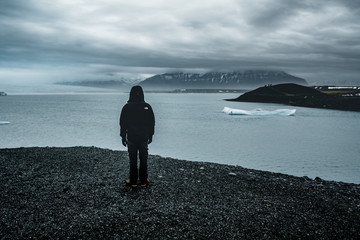 Young man overlooking jokursarlon glacial lagoon on a misty day in south Iceland