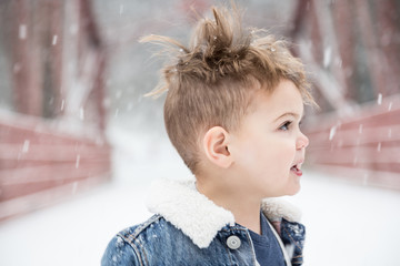 Boy With Blond Hair Looking Away During Snowfall