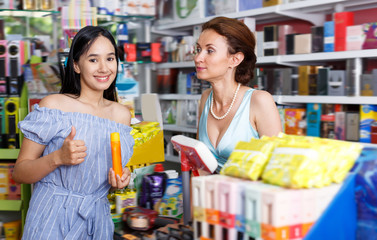 Adult woman seller helping to girl customer