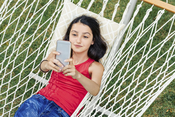 Girl taking selfie while lying in hammock