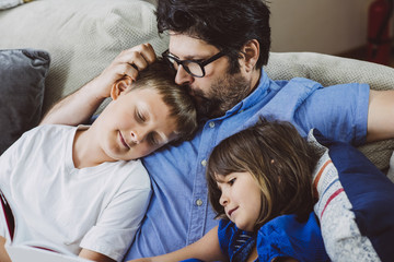 Son and daughter leaning on father while reading book at home