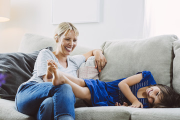 Mid adult woman looking at happy daughter lying on sofa at home