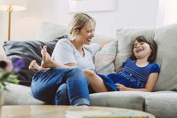 Mid adult woman looking at happy daughter while sitting on sofa at home