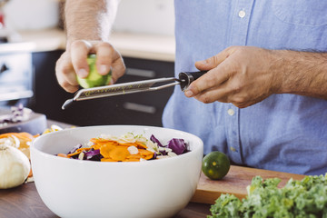 Midsection of mature man zesting lime in salad bowl at kitchen island