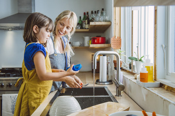 Smiling mother looking at cute daughter washing utensils in kitchen