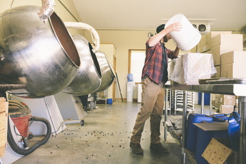 Worker Filling Cardboard Box With Coffee Beans In Industry