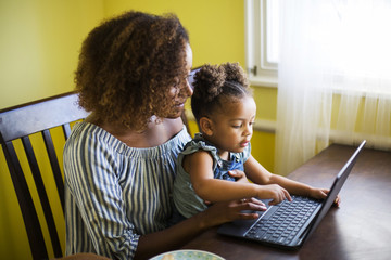 Mid adult woman using laptop with daughter while sitting at table in home