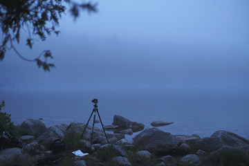Camera on tripod taking photographs of Jordan Pond in foggy weather