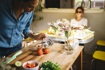 Mid adult woman preparing Mexican salsa at wooden table with friend in background at home