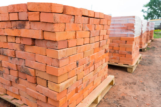 The bricks are stacked on wooden pallets and prepared for sale. Clay brick is an ecological building material.