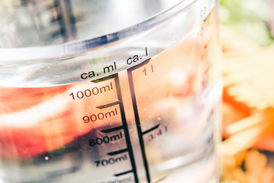 1000 ml - ccm Water In A Measuring Cup Surrounded By Noodles, Onion, Carrots And Spices