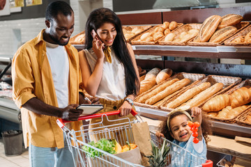Fotobehang Bakkerij african american woman talking on smartphone while her husband and daughter standing near with shopping trolley in supermarket