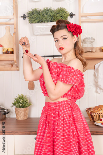 70006dbe4 beautiful young girl with flower in her hair posing in red pin up polka dot  dress