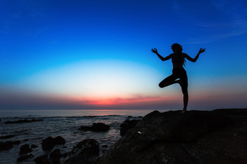 Yoga woman silhouette on the Sea during amazing sunset.