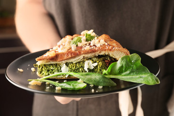 Woman holding piece of tasty pie with spinach on plate, closeup