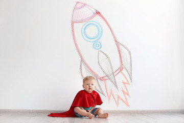 Adorable little child playing astronaut near wall with drawing of spaceship indoors