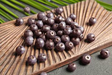 Fresh acai berries on wooden board, closeup