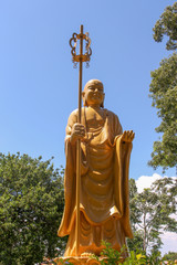yellow buddha at the park in a beautiful sunny day with blue sky