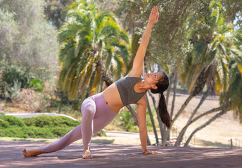 Athletic young woman practicing yoga outdoors in Side Plank Pose