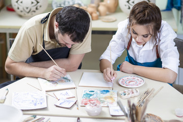 Two Caucasian Ceramists Painting and Glazing Clay Crafts Together in Workshop with Paintbrushes.