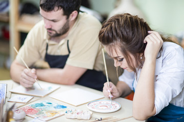 Two Young Caucasian Ceramists Painting and Glazing Clay Crafts Together in Workshop with Paintbrushes.