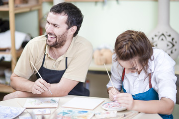 Pottering Ideas. Two Happy Caucasian Ceramists Painting and Glazing Clay Crafts Together in Workshop Using Paintbrushes.