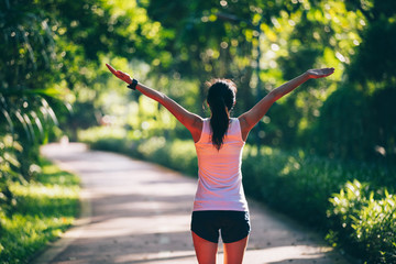 Healthy woman outstretched arms on morning park