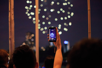 Man holding cellphone with one hand to record beautiful fireworks display
