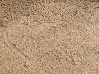 Draw two hearts together on the sand beach.