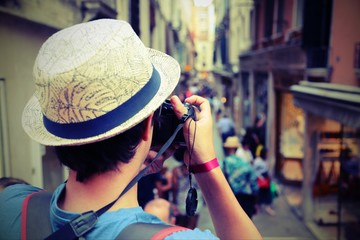 Young boy with digital camera takes many pictures of a narrow st