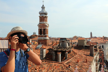 Young photographer with digital camera takes many pictures in Ve